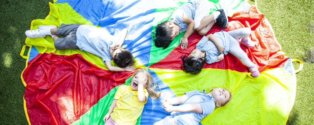 Kindergarten children lying on colourful circle on grass