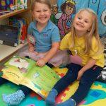 Girls sitting on floor in Kindergarten smiling