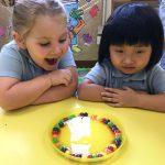 Kindergarten diverse girls looking at M&Ms happily