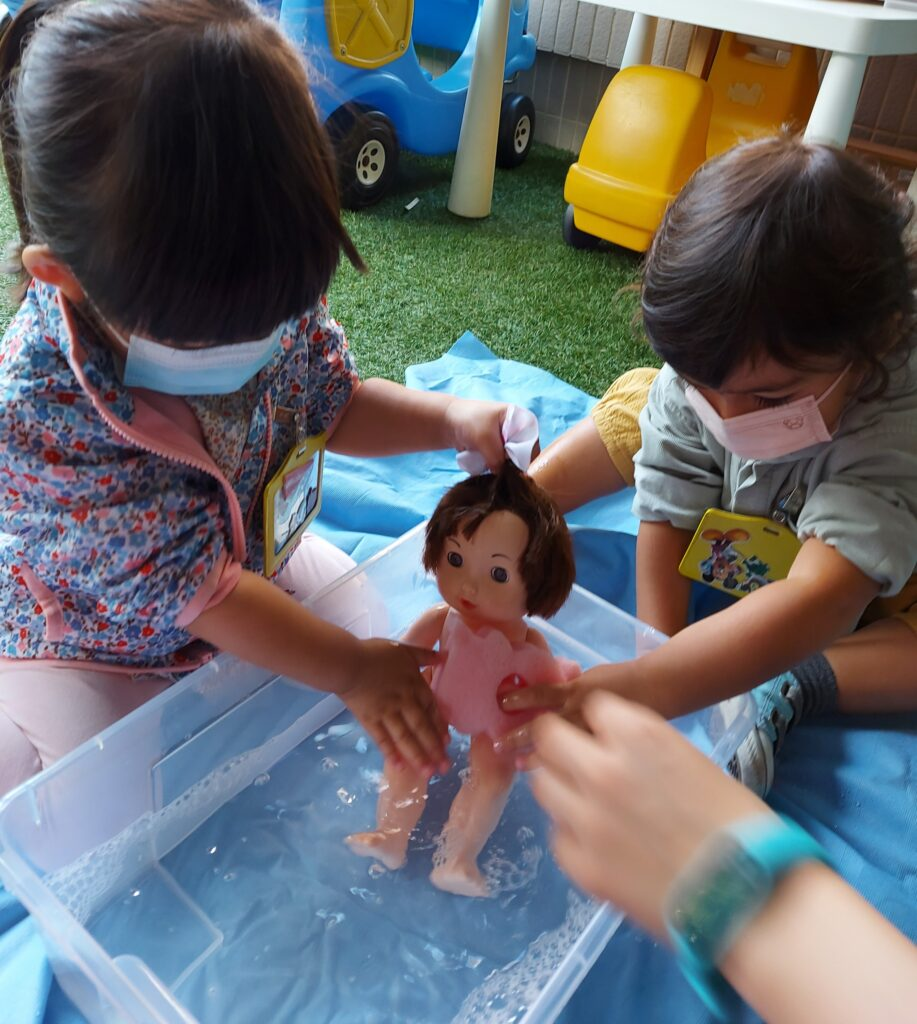 Girls giving doll a bath